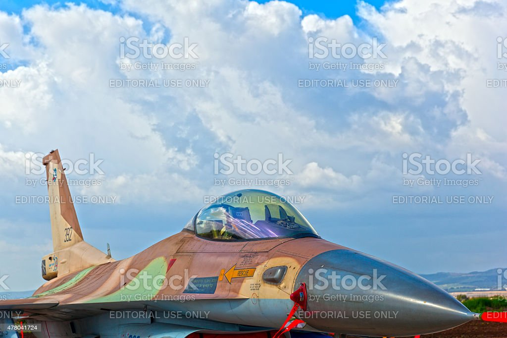 Modern camo painted fighter on cloudscape background stock photo