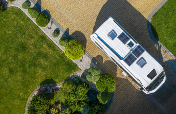 Modern Camper Van with Solar Panels Installed Staying on Residential Driveway Aerial View stock photo