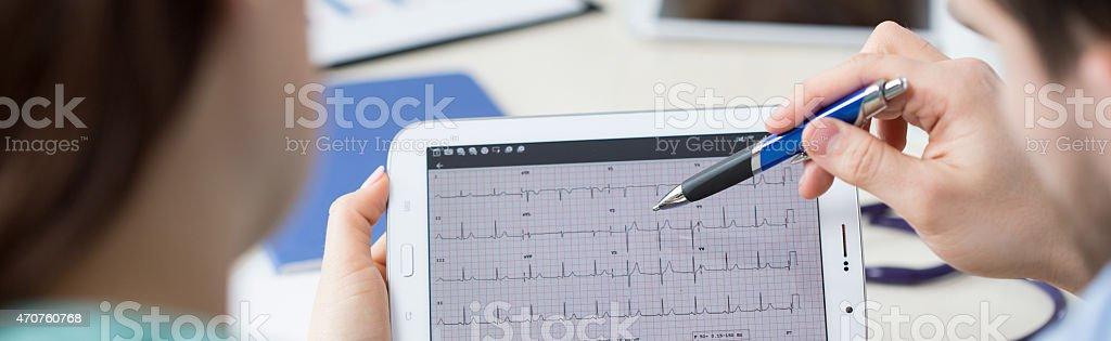 Modern cardiologists analyzing electrocardiogram stock photo