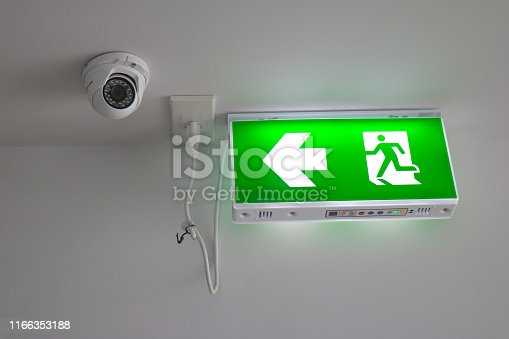 1182906669istockphoto Modern CCTV camera on a wall with LED exit sign,  Close-up Exit neon or led sign in corridor point way out of resident apartment building 1166353188