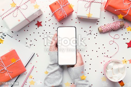 Online Christmas shopping. Modern cellphone with white blank screen in woman hands on background with gifts, copy space