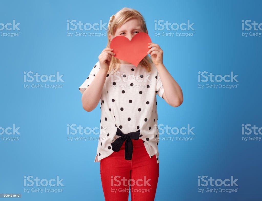 enfant moderne dans un pantalon rouge sur bleu se cachant derrière le coeur de papier - Photo de Bleu libre de droits