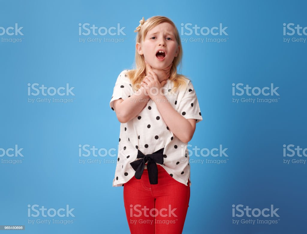 modern child in red pants on blue with neck pain zbiór zdjęć royalty-free