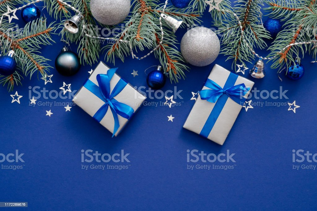 Modern Christmas Decorations Fir Tree Branches Silver Baubles Gift Boxes With Ribbon Bow Confetti On Dark Blue Background Merry Christmas And Happy New Year Concept Flat Lay Top View Stock Photo
