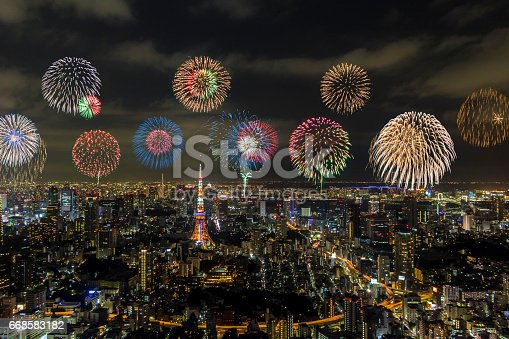 istock modern city night view and skyrocket fireworks 668583182