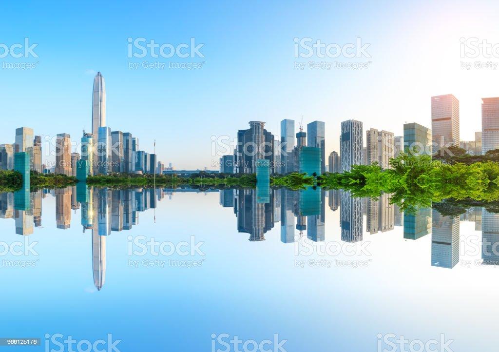 Modern city skyline och vatten speglar i Shenzhen vid soluppgången - Royaltyfri Arkitektur Bildbanksbilder