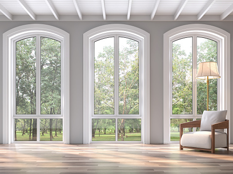 Modern classic living room with nature view 3d render.The Rooms have wooden floors and white wood ceilings.Decorated with white fabric chair,There are arch shape window sunlight shining into the room.