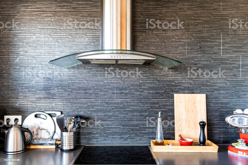 Modern, clean interior of kitchen with cooking utensils, tea pot or kettle, cutting board, coffee maker, electric stove, spices containers, stone wall backsplash and exhaust fan stock photo