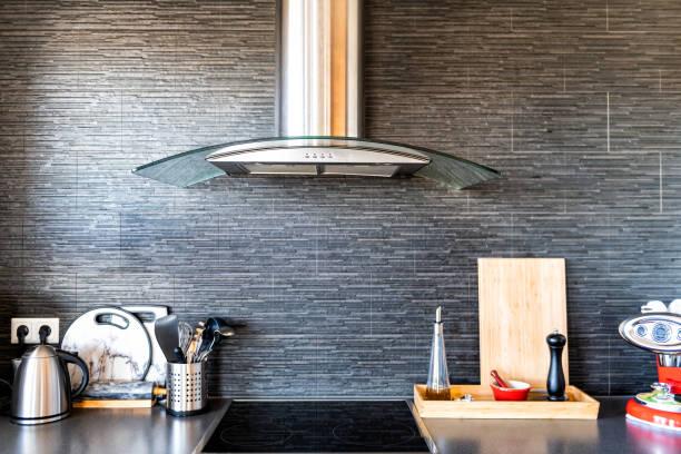 moderne, saubere einrichtung küche mit kochutensilien, tee topf oder wasserkocher, schneidebrett, kaffeemaschine, elektroherd, gewürze behälter, stein wand backsplash und absaugventilator - grillstein stock-fotos und bilder
