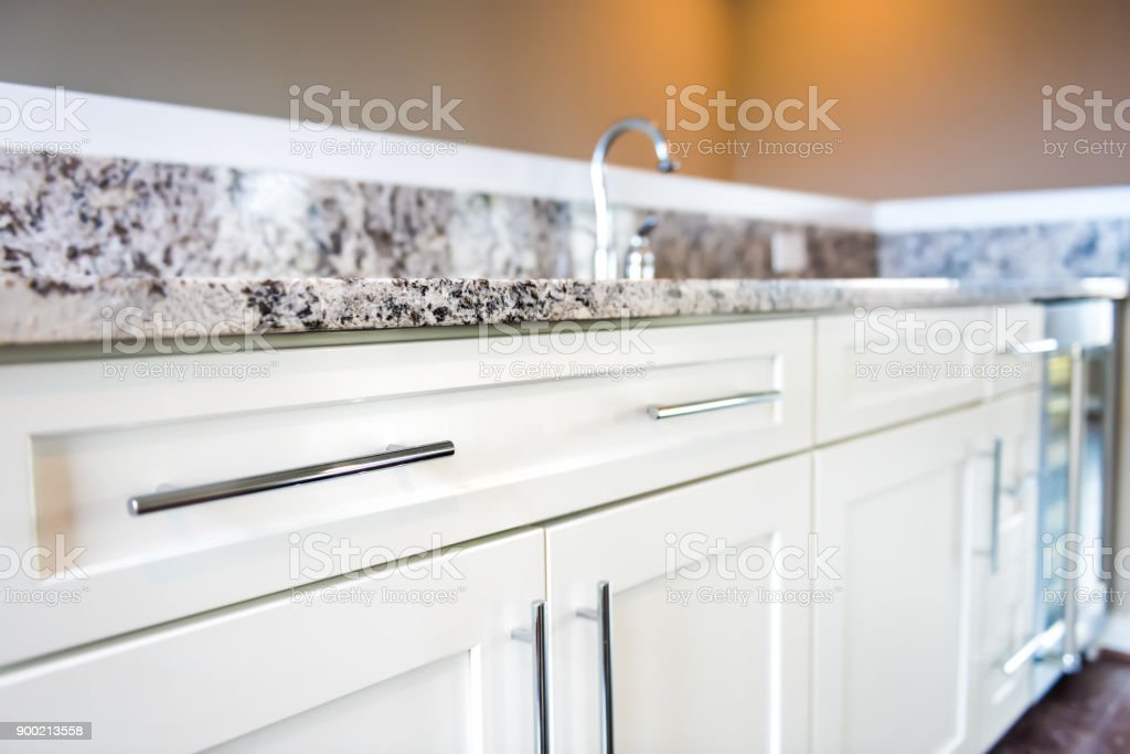 Modern clean wet bar with granite countertop cabinets, faucet in model house, home or apartment, mini fridge stock photo