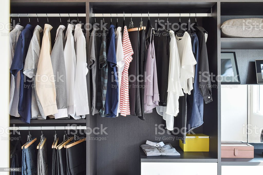 modern closet with row of cloths hanging in black wardrobe stock photo