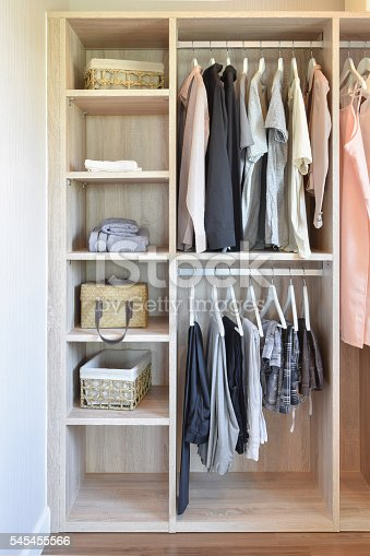 istock modern closet with row of cloths hanging in wooden wardrobe 545455566