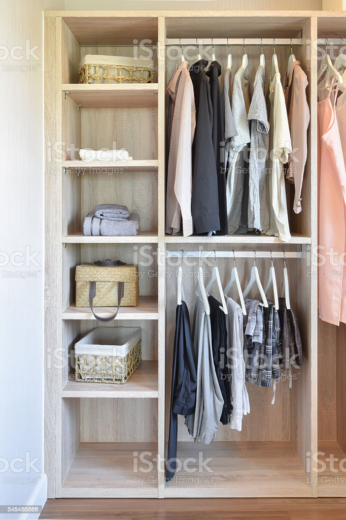 modern closet with row of cloths hanging in wooden wardrobe stock photo