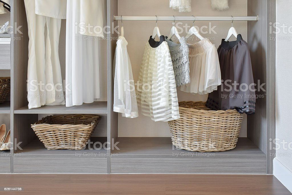 modern closet with wooden basket and white dress in wardrobe stock photo