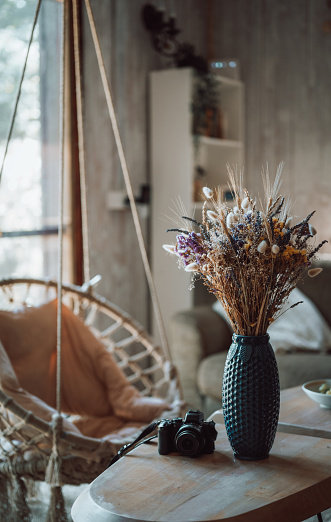 Comfort room with furniture in the house with modern boho design interior and a cozy rope swing next a window The concept of home life, home comfort.