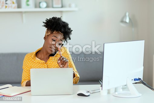 African American Businesswoman Busy With Her Work in the Office. Beautiful Woman Working in Modern Office While Talking on the Smartphone. Remote Job, Technology and People Concept