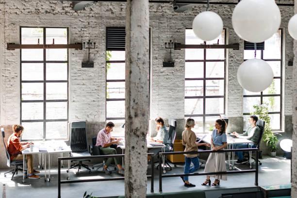 moderne bedrijven: groep van jonge zakenmensen bij een ruime loft open ruimte coworking office working together - groothoek stockfoto's en -beelden