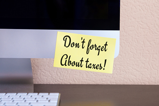 istock modern computer with reminder yellow sticker note with text: don't forget about taxes! 943062184
