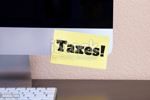 istock modern computer with reminder yellow sticker note with text: taxes! 943062164
