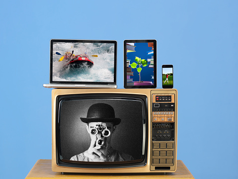 Old fashioned television,modern computer,tablet pc,smartphone on desk.The background is blue wall.There is a black and white image on tv screen while color images on other screens.Shot in studio with medium format camera.