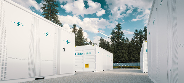 Modern container battery green energy storage system accompanied with solar panels and wind turbine situated in nature 3d rendering.