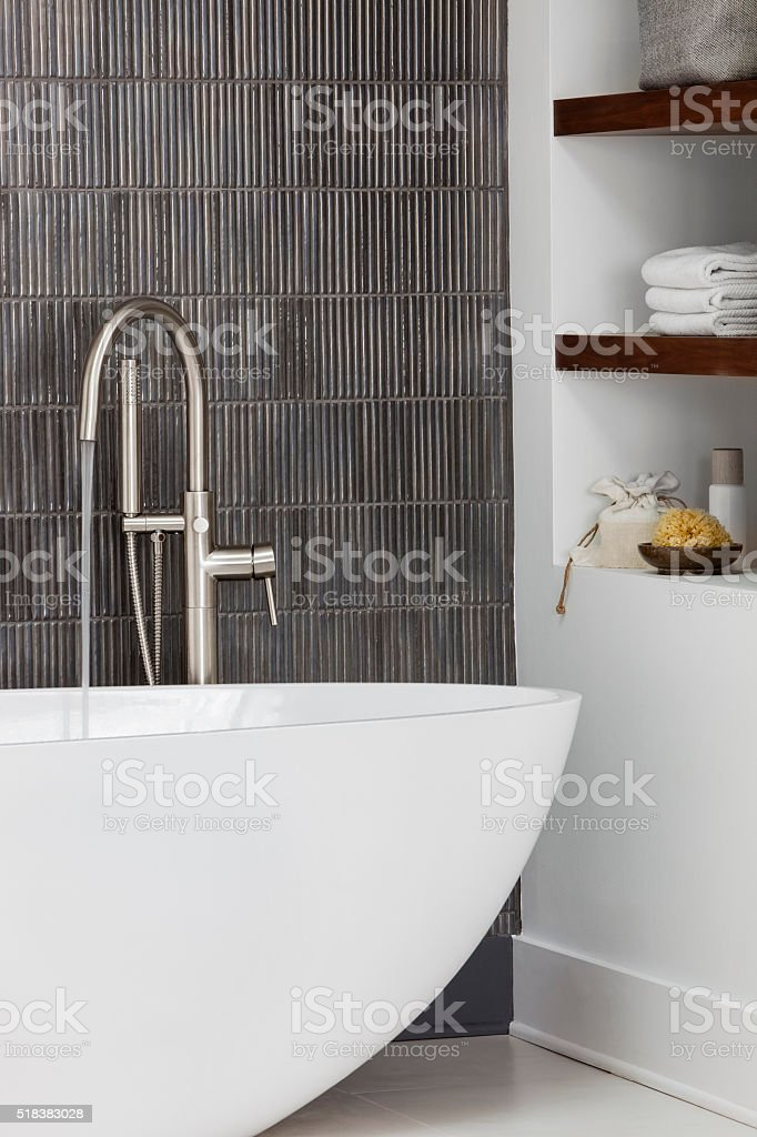 Modern Contemporary bath with water running from stainless faucet. stock photo