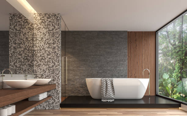 Modern contemporary bathroom with nature view 3d render Modern contemporary bathroom 3d render. There are gray nature stone brick wall, wood floor.The room has large windows. Looking out to see the garden view. bathtub stock pictures, royalty-free photos & images