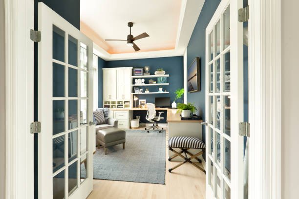 Modern Contemporary Interior Design of Home Office Room +++ NOTE TO INSPECTOR +++ 6 framed photos on shelf and one hung on wall, all 7 photo artwork are my work and is currently in the iStock collection. See Property Release +++  A modern cozy home office interior design with computer desk and office chair. an arm chair, interior rug and a window view. ceiling fan stock pictures, royalty-free photos & images