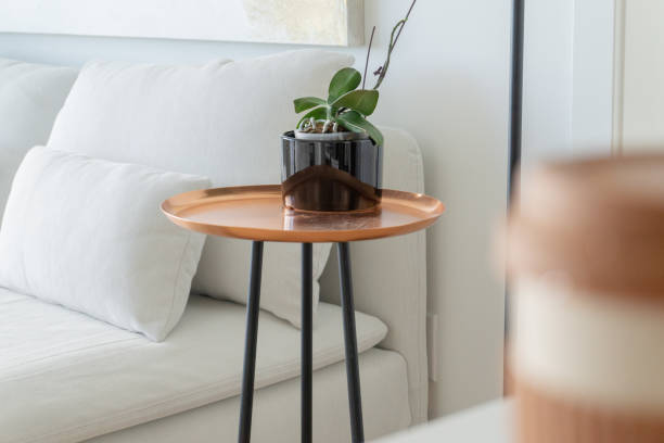 moderne, kupfer tablett beistelltisch mit schwarzen beinen, neben einem weißen futon couch, konzentrierte sich in der ferne mit einer orchidee topfpflanze - couchtisch metall stock-fotos und bilder