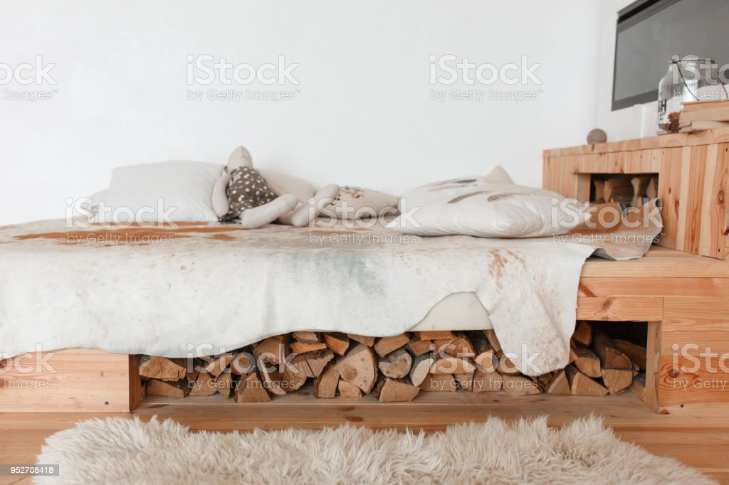 Modern country house interior with wooden bed, firewood, fireplace stock photo