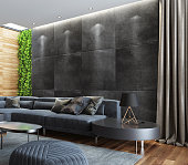 Sophisticated spacious living room with lots of natural light. Dominant gray elements are combined with wood and vertical green wall as a bold accent to the room. Elegant gray velvet sectional sofa with attached side table and decorative modern velvet and silk cushions is placed in front of walls with variety in textures. Two elliptically shaped black metal, copper and white glass glass coffee  tables are placed on a thick gray carpet. In addition to sofa there is a contemporary irregularly shaped gray velvet ottoman. Modern country style luxury house living room with plant vertical wall.