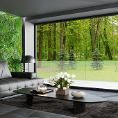 Modern living room with modern black leather sofa and furniture. Big plant wall next to window.\nBackground forest nature concept. Country villa interior.