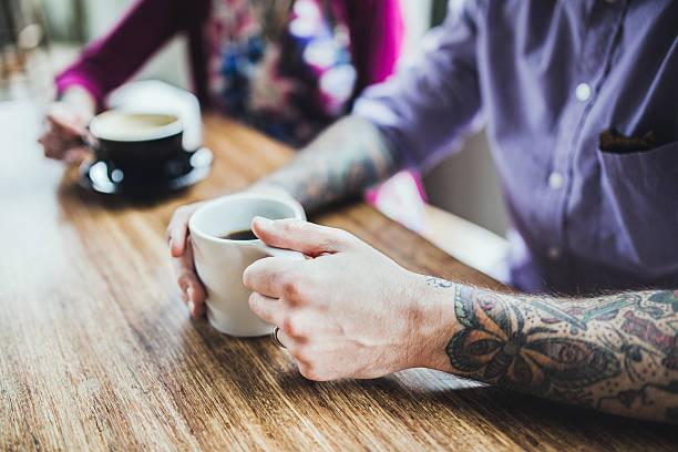 moderne paar im café - kaffeetasse tattoo stock-fotos und bilder
