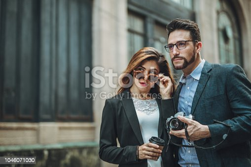Man and woman, young heterosexual couple downtown on the street, man with camera, woman with coffee cup.