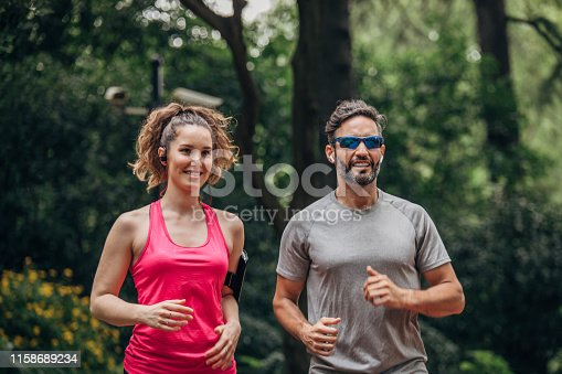One young couple in sport clothing listening to music on headphones and jogging in park.