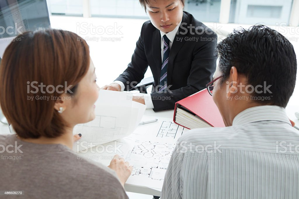 Modern couple listening to manager explanation about conditions of mortgage stock photo