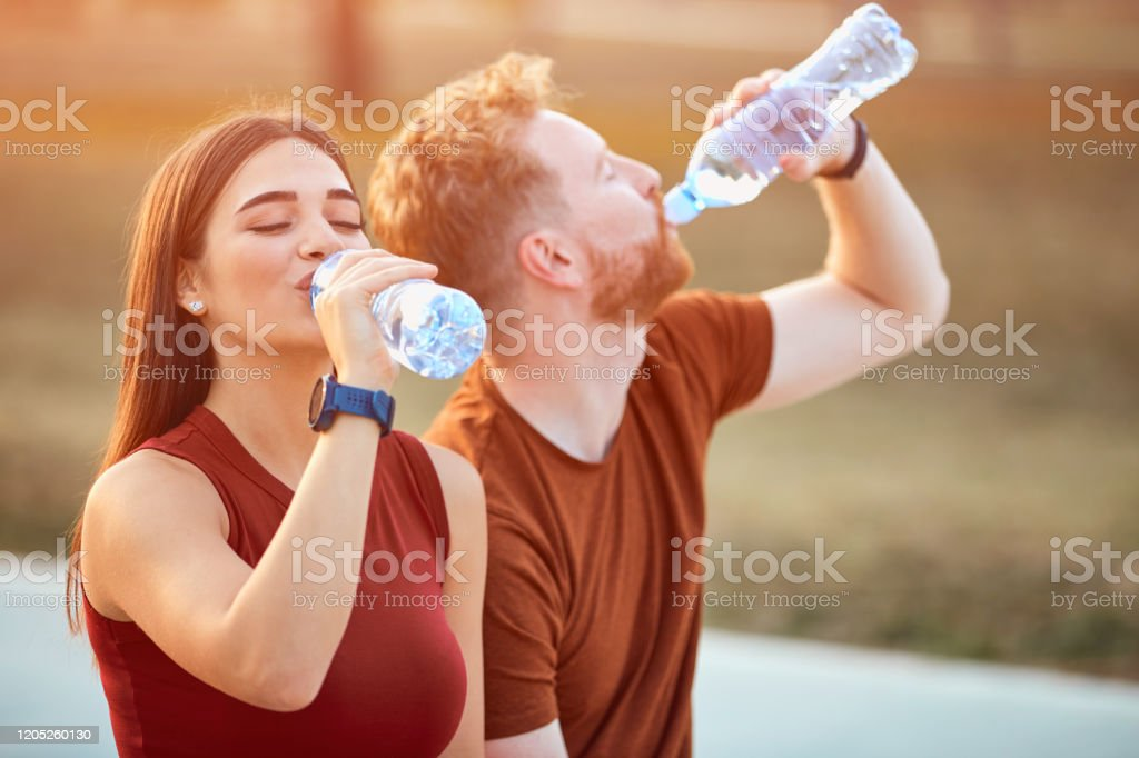 Modern couple making pause in an urban park during jogging / exercise. Modern couple making pause in an urban park during jogging / exercise. Adult Stock Photo