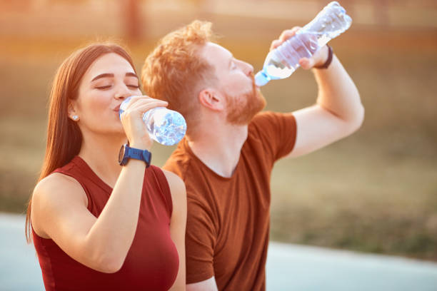 Modern couple making pause in an urban park during jogging / exercise. stock photo