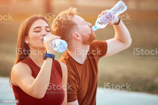 Modern Couple Making Pause In An Urban Park During Jogging Exercise Stock Photo - Download Image Now