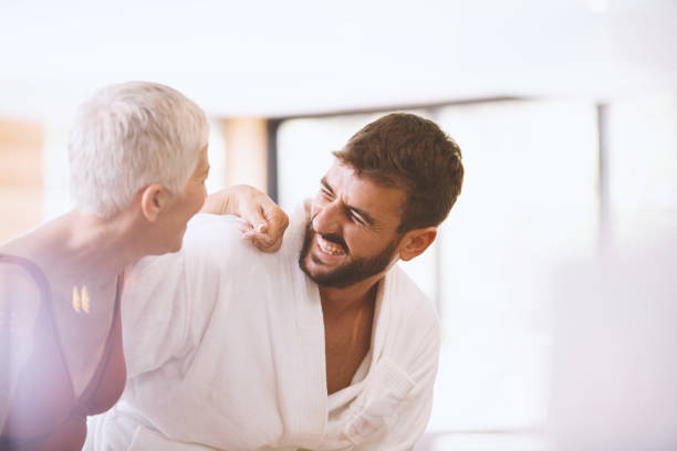 Modern couple Side view of a mature woman and younger man laughing together. They are enjoying vacation at the spa. age contrast stock pictures, royalty-free photos & images