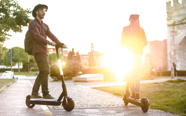 Modern couple using electric scooter in city park - Milenial students riding new ecological mean of transport - Green eco energy concept with zero emission -Bright warm filter with sunshine halo stock photo
