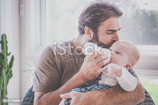 istock Modern Dad Feeding his Baby Boy with Milk Bottle 585076998