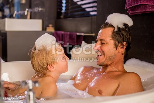 Modern dad and son taking a bubble bath together and playing with soap suds at home in bathroom