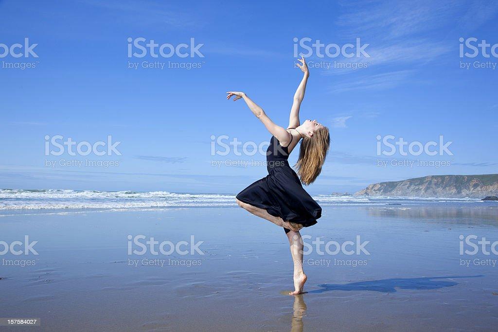 modern dancer standing on one leg at the beach