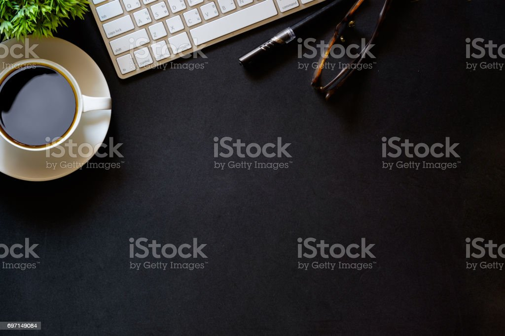 Modern dark surface office desk table with computer and cup of...