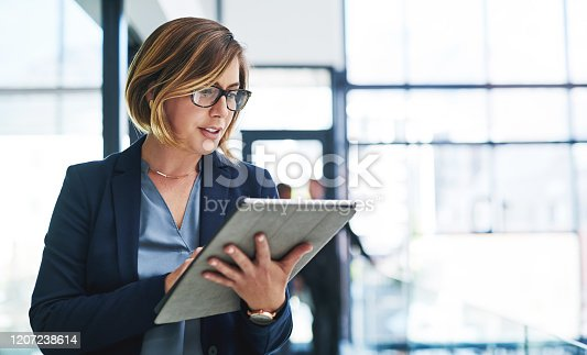 Cropped shot of an attractive young businesswoman using a digital tablet in an office with her colleagues in the background