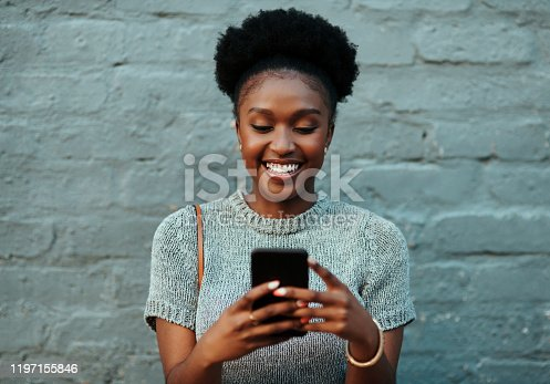 Shot of an attractive young creative businesswoman using her cellphone while standing against a grey wall outdoors