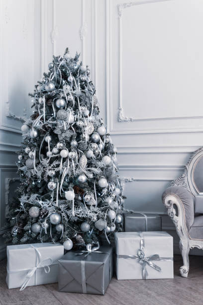 Modern decorated Christmas tree in white and silver colors with gift boxes stock photo