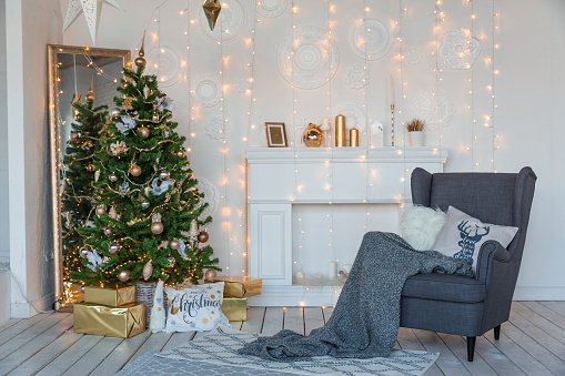 Modern design room in light colors decorated with Christmas tree and decorative elements.