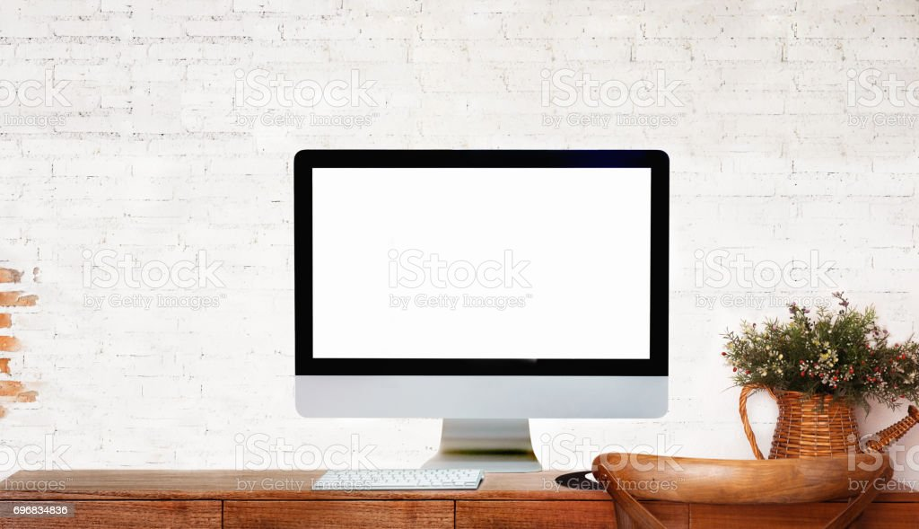 Modern Desktop Computer showing Blank Screen on wood Table over Brick...